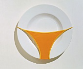 Empty White Plate with an Orange Bikini Bottom on It