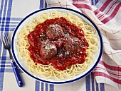 Plate of Spaghetti and Meatballs on Blue and White Table Cloth; Fork