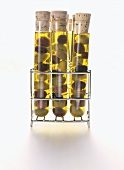 Assorted Olives in Oil in Test Tubes on Storage Rack; White Background