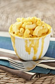 Small Bowl of Macaroni and Cheese with Cheese Dripping Down Sides of Bowl