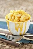 Macaroni and Cheese in Schale mit überfliessender Käsesauce