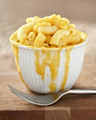 Bowl of Macaroni and Cheese with Cheese Sauce Dripping Down Side of Bowl