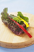 Two Swiss Chard Leaves, Red and Yellow on a Cutting Board