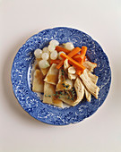 Plate of Chicken with Dumplings, Carrots and Pearl Onions on a White Background