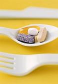 Assorted Vitamins on a Plastic Spoon; Plastic Fork