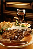Grilled Porterhouse Steak on a Plate with a Knife and a Glass of Red Wine
