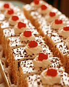 Rows of Torte Slices Topped with Maraschino Cherries
