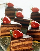Slices of Layered Chocolate Mouse Torte Topped with Strawberries