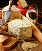 Assorted Wheels of Cheese with Glasses of Red Wine