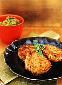 Three Goan Spiced Crab Cakes on a Dish; Avocado Salad