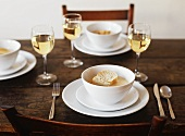 Table Set with Bowls of Lobster Bisque Topped with Bread; White Wine