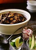 Pork Rib and Black Bean Chili in a Pot; Lime; Red Onion and Avocado