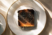 Burnt Piece of Toast on a Plate