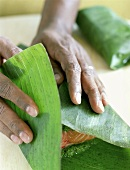 Hands Wrapping Salmon in Banana Leaves