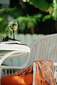 Glass of White Wine with Books and Sunglasses on an Outdoor Table