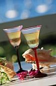 Zwei Weissweingläser auf Tisch im Freien mit Muscheldeko