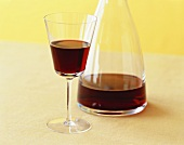 A Glass and Carafe of Red Wine on Yellow Background