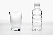 Glass and Bottle of Water on a White Background