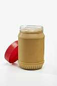 Opened Jar of Peanut Butter on a White Background