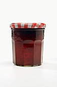 A Single Jar of Strawberry Jam on a White Background