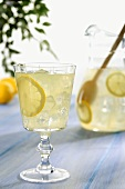 Glass of Lemonade on Table with Pitcher