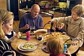 Familie isst Spaghetti und Salat in der Küche