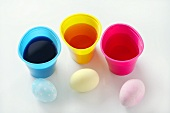 Drei gefärbte Eier neben Becher mit Eierfarben