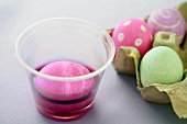 An Egg in a Cup of Pink Easter Egg Dye