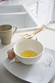 Bowl with Cracked Eggs, Egg Shells and Whisk on Kitchen Counter