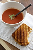 Partially Eaten Grilled Cheese Sandwich with a Bowl of Tomato Soup