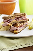 Halved Grilled Ham and Cheese Sandwich on a Plate