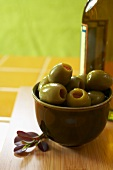Organic Green Olives in a Bowl with a Bottle of Olive Oil