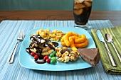 Junk Food auf Teller, Glas Cola im Hintergrund