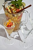 White Wine Sangria with Chopped Fruit in a Glass and Pitcher