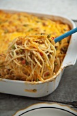 Scooping Turkey Tetrazzini From Casserole Dish