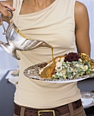 Woman pouring gravy over roast turkey with accompaniments