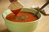 Hand dipping a cracker in tomato soup