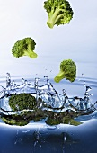 Broccoli florets falling into water
