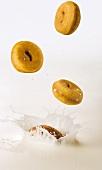 Doughnuts falling into milk