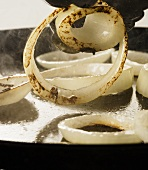 Onion rings being fried in a pan (close up)