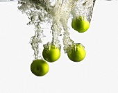 Green Apples Splashing into Water