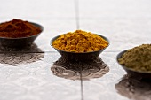 Three Small Bowls of Assorted Ground Spices