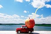 Apfel mit Strohhalm auf Modelllastwagen am Meer