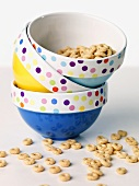 Three Stacked Bowl with Cereal In and Around Them