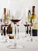 Mehrere fast leere Rotweingläser & Rotweinflaschen