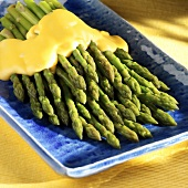 Cooked Asparagus on a Blue Serving Plate with Cheese Sauce