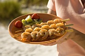 A Woman Holding a Plate of Skewered Shrimp at the Beach