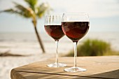 Two Glasses of Red Wine on a Table at the Beach