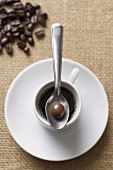 Chocolate Covered Espresso Bean on a Spoon on a Cup of Espresso