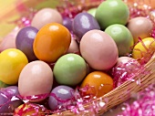 Candy Eggs in a Basket with Pink Grass, Close Up